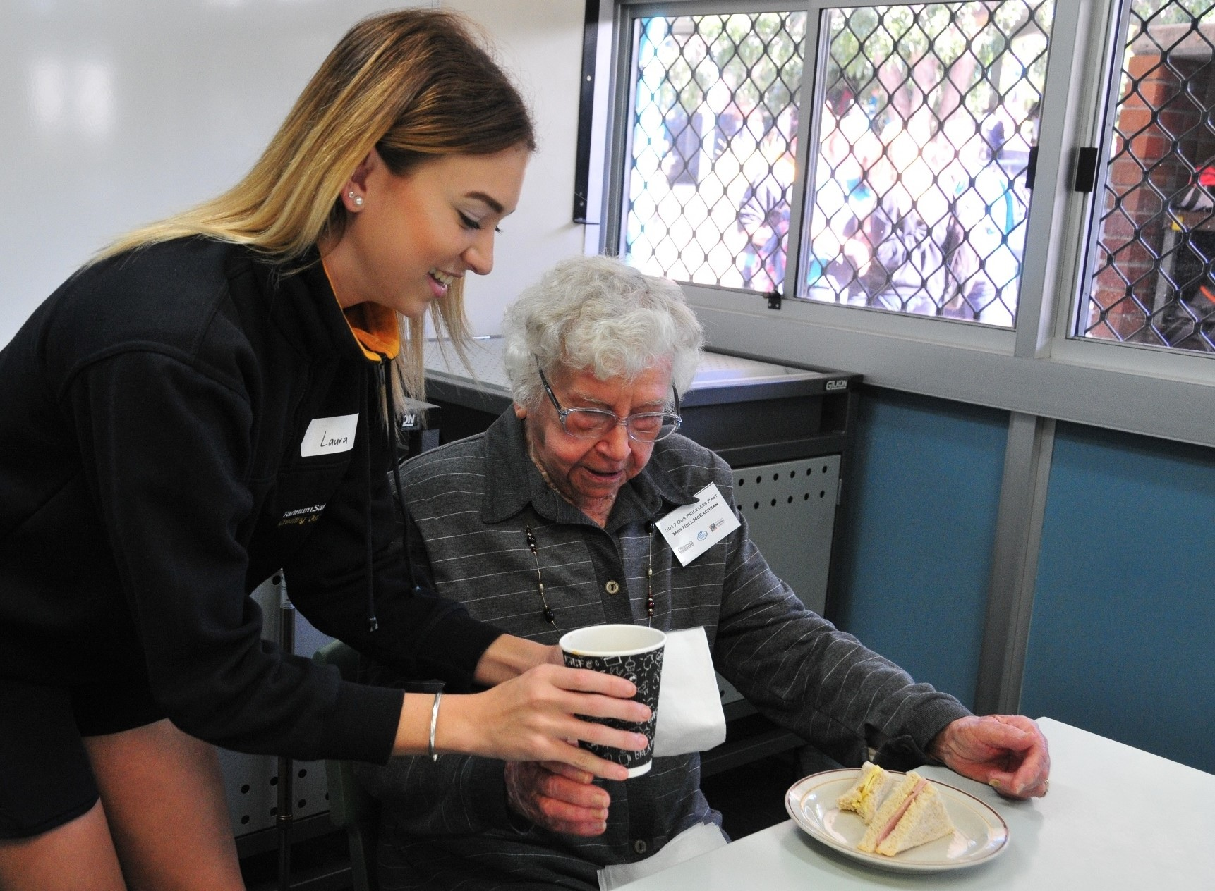 Tannum Sands State High School Year 9's Laura Grummitt serves morning tea to Mrs Nell McEachran, during interviews at the school. (Image: D Paddick)