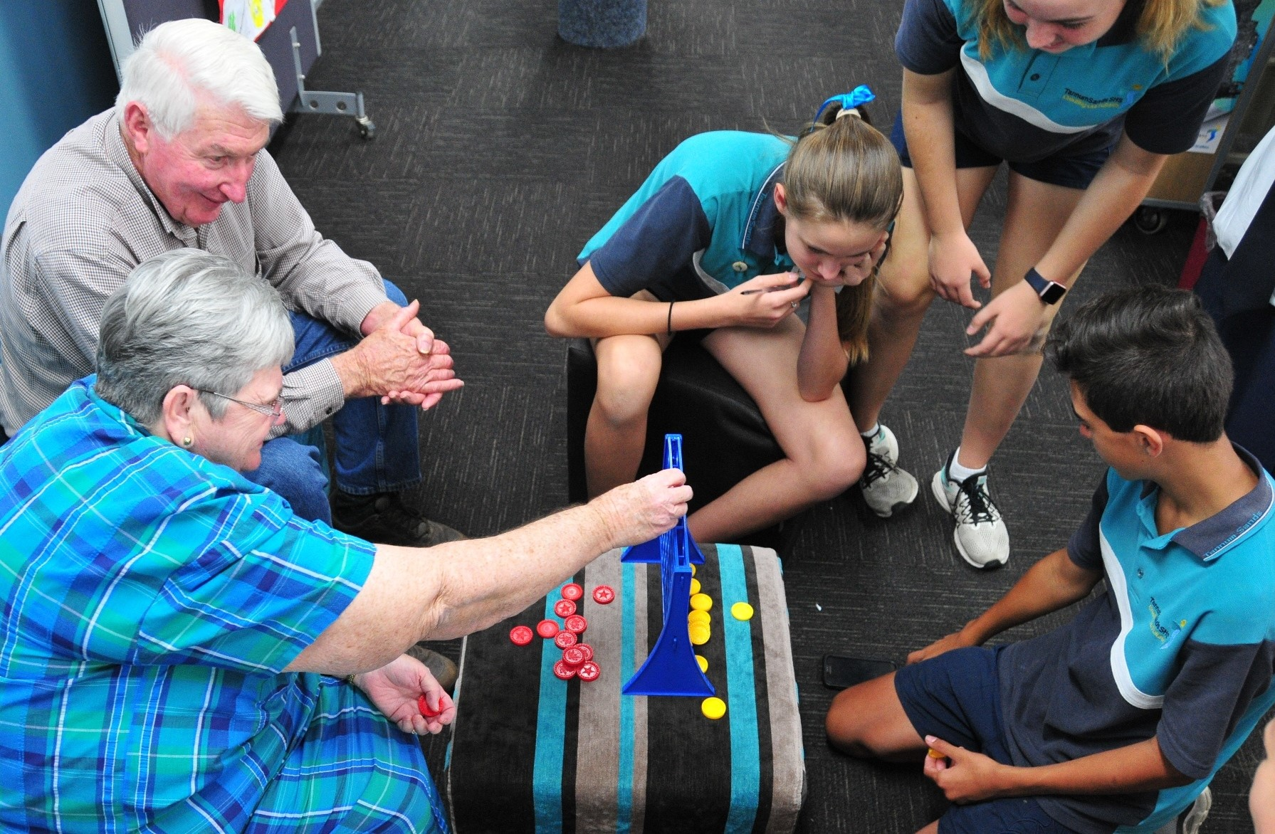 Tannum Sands State High School Year 9 students battle a game of Connect Four with Special Seniors Pat and Graham Bruce. (Image: D Paddick)